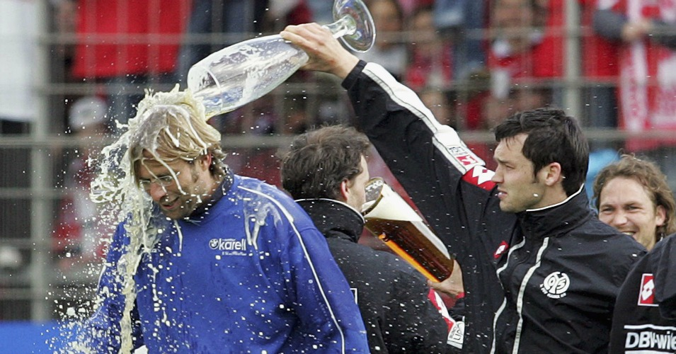 MAINZ, GERMANY - MAY 7: Benjamin Auer of Mainz pours beer on headcoach Juergen Klopp after the Bundesliga match between FSV Mainz 05 and FC Bayern Munich at the Bruchweg Stadium on May 7, 2005 in Mainz, Germany. Mainz will now stay in the top division. (Photo by Alexander Heimann/Bongarts/Getty Images) *** Local Caption *** Benjamin Auer;Juergen Klopp