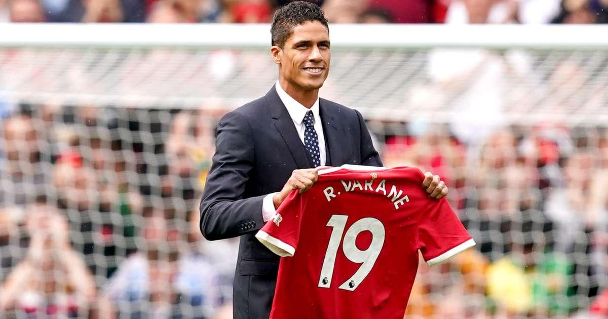Raphael Varane holding his new Manchester United shirt at Old Trafford