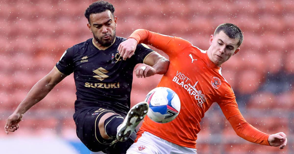 A contest for possession between MK Dons star Louis Thompson and Blackpool's Ben Woodburn