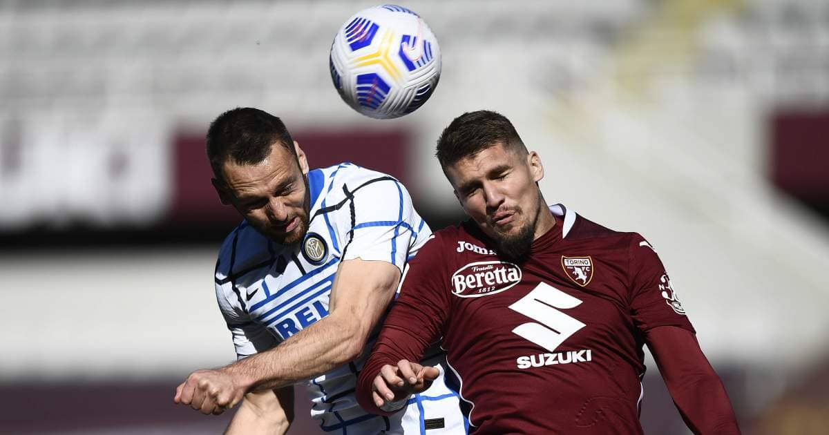 Stefan De Vrij of Inter and Lyanco of Torino competing for a header
